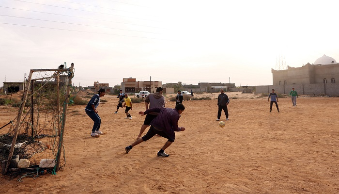 Young people from the city of Sirte, 450 kilometres east of the Libyan capital Tripoli, play football after returning to the outskirts of the city on December 20, 2016, after pro-government Libyan forces of the National Accord (GNA) drove the Islamic State group out of its Libyan stronghold earlier this month.   / AFP PHOTO / MAHMUD TURKIA